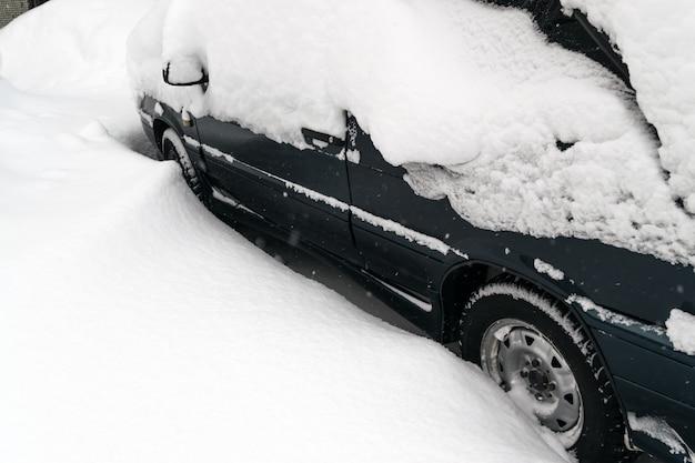 Coche cubierto de nieve después de una ventisca invernal
