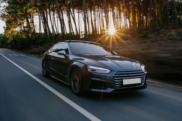 Coche deportivo negro carretera conducir en la puesta de sol.