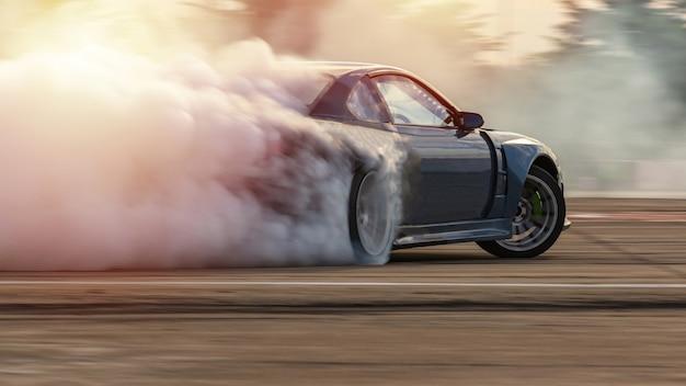 Coche a la deriva, coche de deriva de carrera de difusión de imagen borrosa con mucho humo de neumáticos en llamas