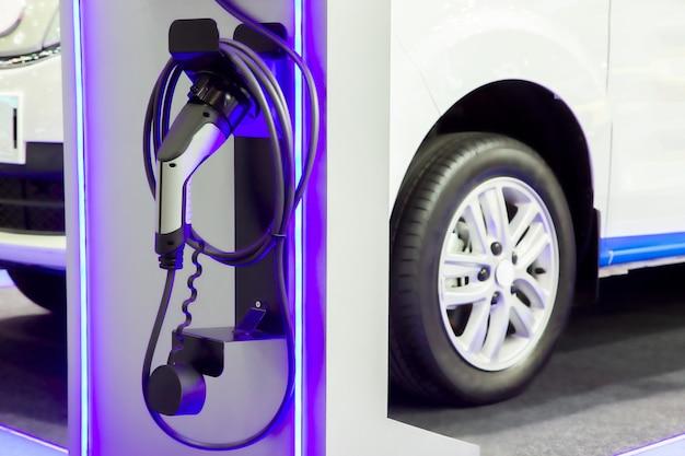 Coche eléctrico de carga en el estacionamiento con estación de carga de vehículos eléctricos en la calle de la ciudad.