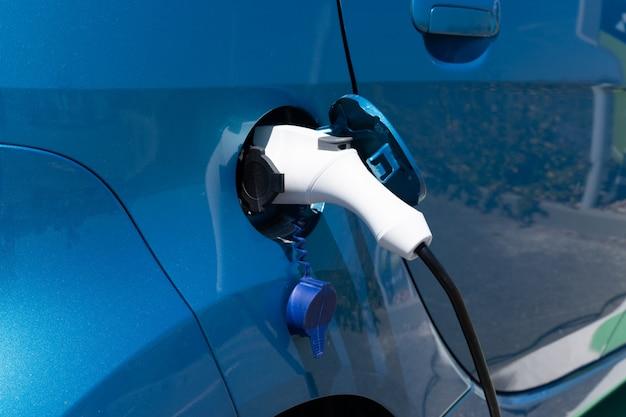 Coche eléctrico que carga la energía de la batería en la estación vehículo azul
