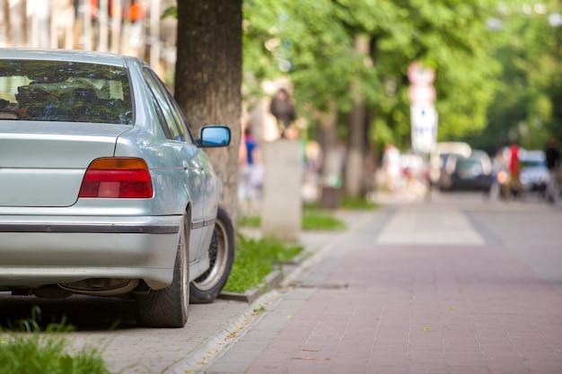 Coche estacionado en la calle verde en zona peatonal con poca gente en día de verano.
