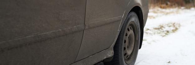 Coche gris muy sucio en otoño o invierno en el barro. bandera