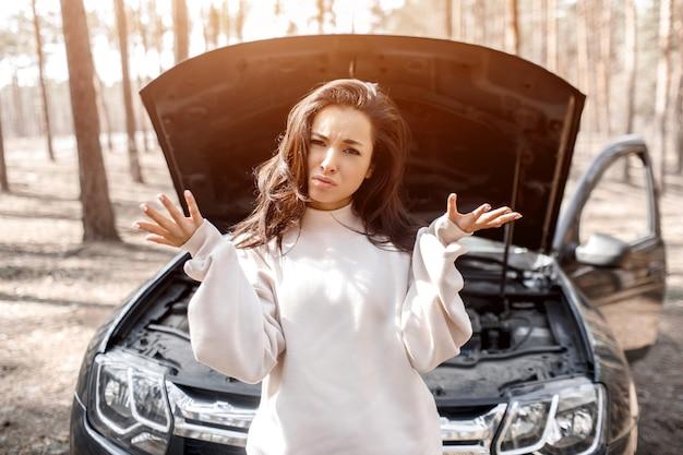 El coche se ha averiado. accidente en la carretera. la mujer abrió el capó y revisó el motor y otras partes del automóvil.