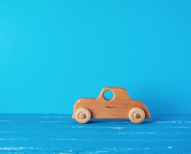 Coche infantil de madera sobre un fondo azul.