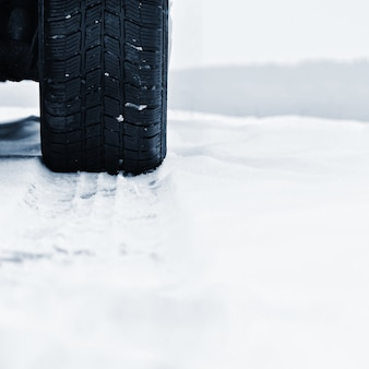 Coche en invierno. neumático en una carretera nevada con mal tiempo.