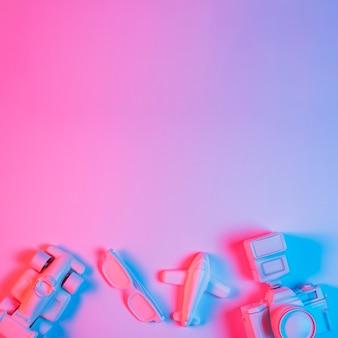 Coche de juguete; avión; espectáculo y cámara dispuestos en el fondo de un fondo rosa con luz azul.
