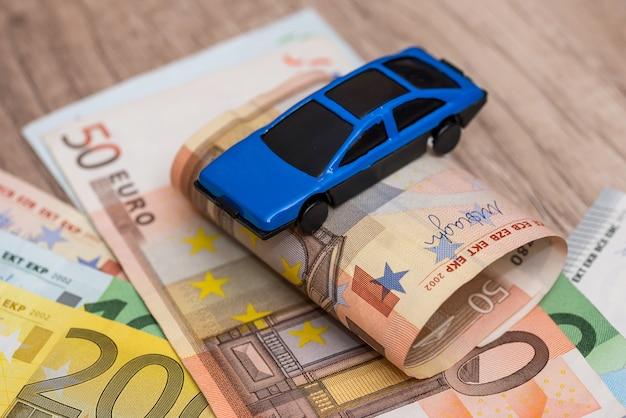 Coche de juguete azul en billetes en euros