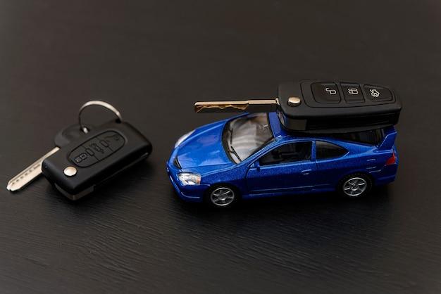 Coche de juguete azul con llaves en la mesa oscura