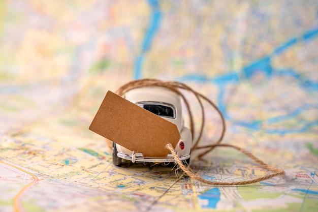 Coche de juguete blanco para viajar con una hoja de papel en blanco para el texto en el mapa