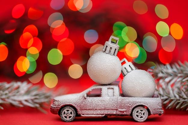 Coche de juguete cubierto de nieve con bolas de navidad sobre fondo rojo bokeh concepto de navidad