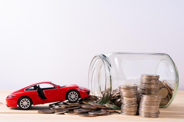 Coche de juguete de lujo rojo junto al frasco de vidrio con monedas en la mesa de madera y pared blanca