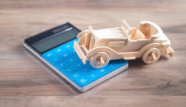Coche de juguete de madera y calculadora en la superficie de madera.