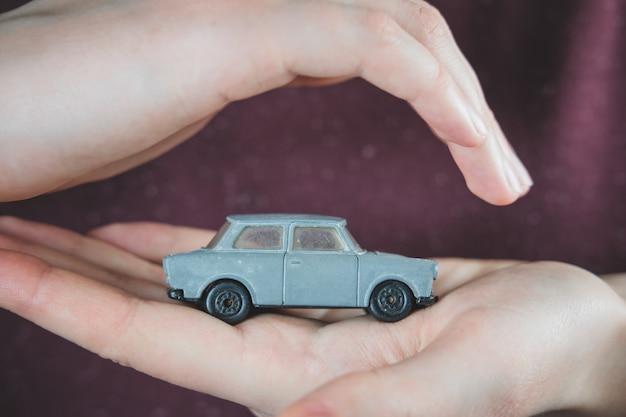 Coche de juguete en manos humanas.