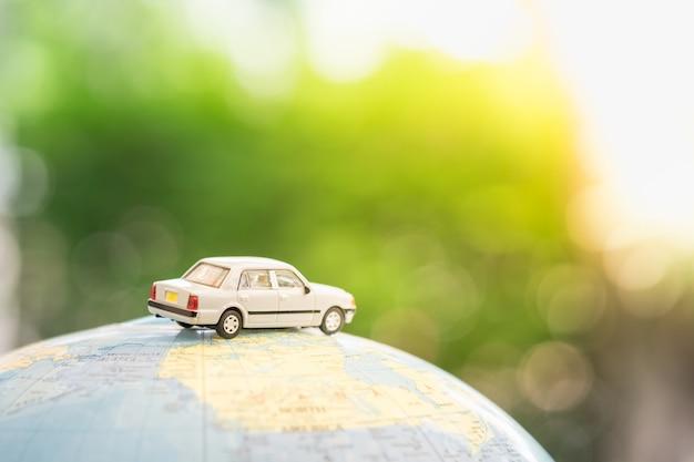 Coche de juguete en miniatura en globo de mapa mundial con naturaleza verde