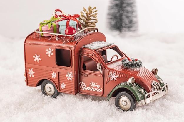 Coche de juguete pequeño decorado con adornos sobre nieve artificial con un árbol de navidad en el fondo
