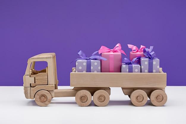 Coche de juguete con regalos en cajas.