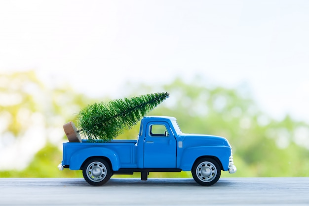 Coche de juguete retro azul entregando regalos de navidad o año nuevo, aislado en blanco