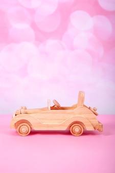 Coche de juguete retro de madera sobre un fondo rosa con bokeh
