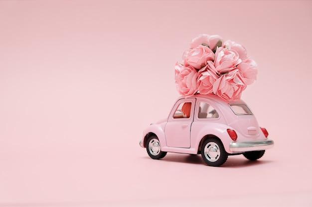 Coche de juguete retro rosa entrega ramo de flores