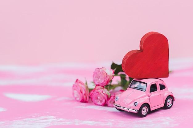 Coche de juguete retro rosa ofrece un corazón rojo sobre fondo rosa. postal del 14 de febrero, día de san valentín. entrega de flores día de la mujer.