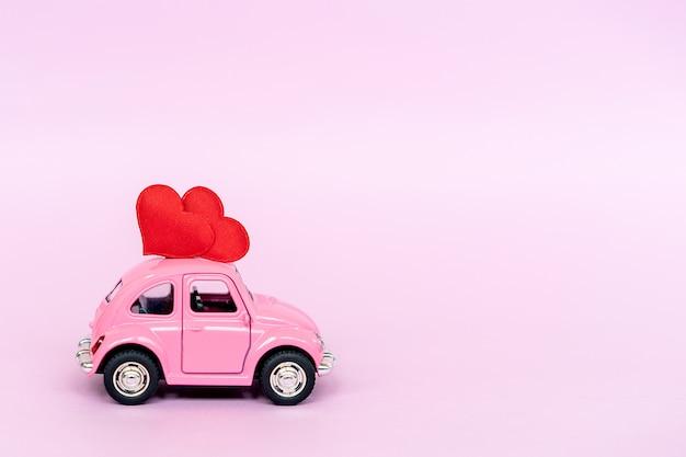 Coche de juguete retro rosa que entrega corazón artesanal para el día de san valentín