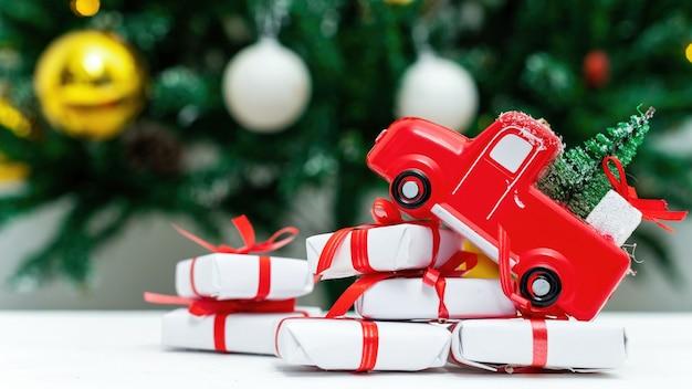 Coche de juguete rojo con árbol de navidad y un montón de regalos debajo. árbol de navidad en el fondo