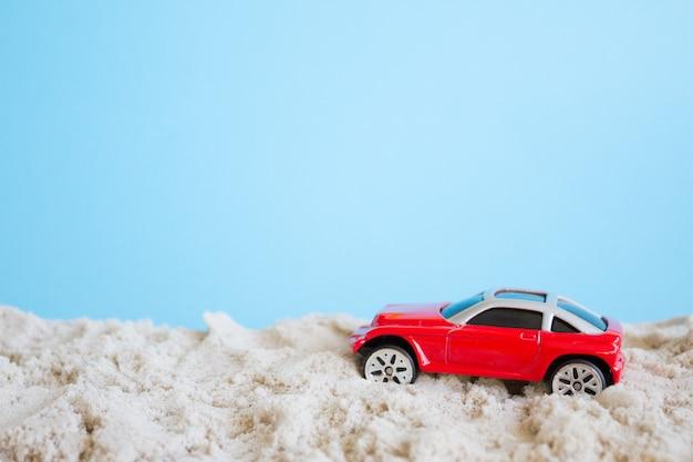 Coche de juguete rojo, concepto de verano. coche en una playa de arena