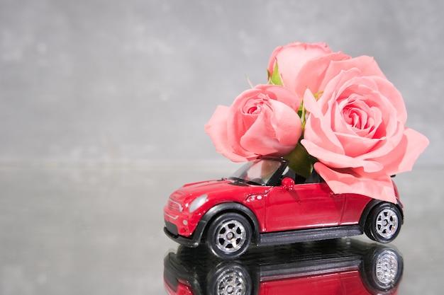 Coche de juguete rojo entregando ramo de flores rosas rosadas