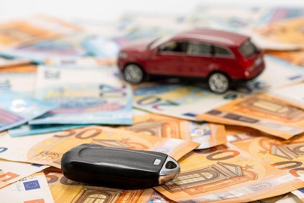 Coche de juguete rojo y llave en la pila de billetes en euros, comprar o vender un coche, alquilar un coche o un concepto de seguro