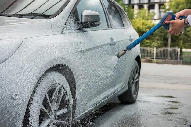 Coche de limpieza de manos femeninas en servicio con herramientas de espuma de jabón y agua. lavar auto