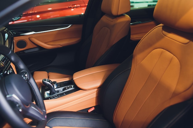 Coche de lujo moderno en el interior. interior del coche moderno de prestigio. cómodos asientos de cuero marrón. cabina de piel perforada naranja.