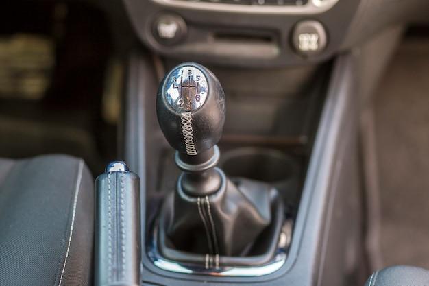 Coche lujoso interior de cuero negro. detalle de primer plano del freno de mano freno manual y palanca de cambios en el tablero borroso. transporte, diseño, concepto de tecnología moderna.