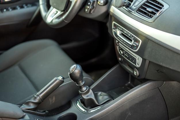 Coche lujoso interior de cuero negro. freno manual y palanca de cambio manual. transporte, diseño, concepto de tecnología moderna.