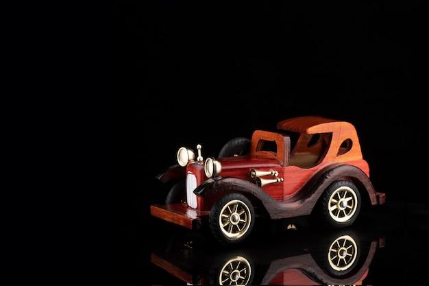 Coche de madera de juguete de estilo retro sobre superficie reflectante.
