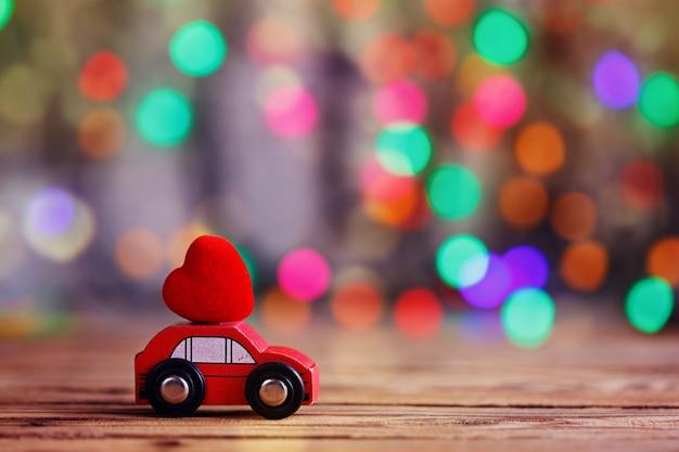 Coche miniatura con un corazón rojo en el techo. concepto de vacaciones amor