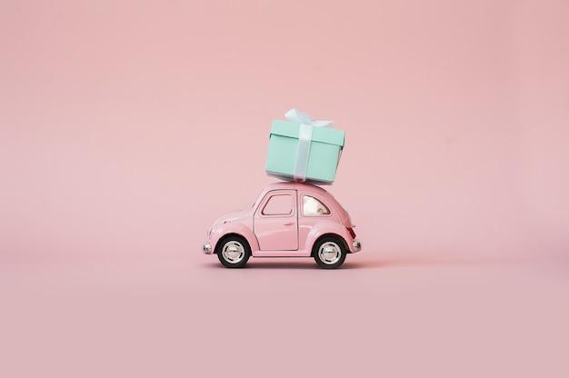 Coche modelo retro del juguete rosado que entrega la caja de regalo en fondo rosado