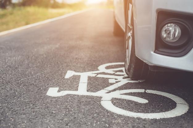 Coche moderno que se ejecuta en la carretera de asfalto / carril de bicicleta y la banda de rodadura en señal de bicicleta blanca