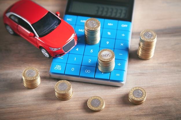 Coche, monedas y calculadora en el escritorio.