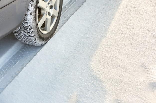Coche en movimiento en carretera nevada, ruedas de neumáticos de goma en nieve profunda. transporte, diseño y seguridad.