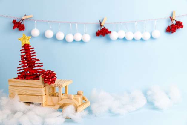 Coche de navidad de juguete de madera sobre fondo azul.