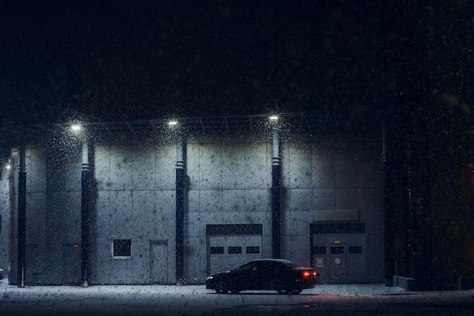 Coche negro estacionado cerca del edificio de oficinas en la noche de invierno en tormenta de nieve fuerte. Automóvil cerca del servicio de automóviles en la noche. Máquina cerca de la puerta automática para mantenimiento. Arquitectura moderna en la noche oscura.