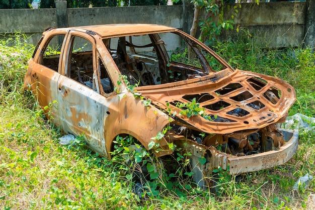 Coche oxidado roto debido al accidente en el césped