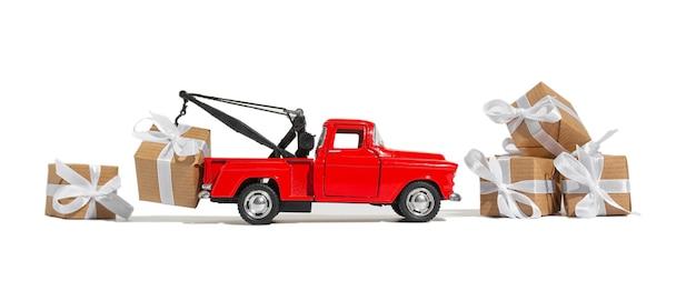 Coche pickup rojo con un regalo para las vacaciones sobre un fondo blanco aislado. concepto de navidad y año nuevo