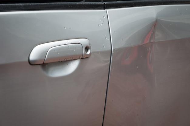 Coche de la puerta con daños por accidente con abolladura en el lado izquierdo en el día lluvioso