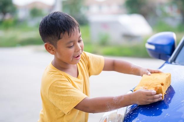 Coche que se lava del muchacho asiático del niño