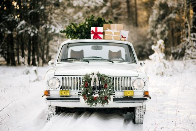 Coche retro con regalos y árbol de navidad en invierno bosque nevado y hermosa corona de navidad.