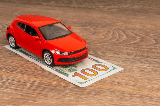 Coche rojo y billete de 100 dólares, concepto de seguro