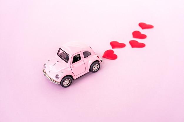 Coche rojo del juguete retro rosado en fondo rosado con confeti del corazón.