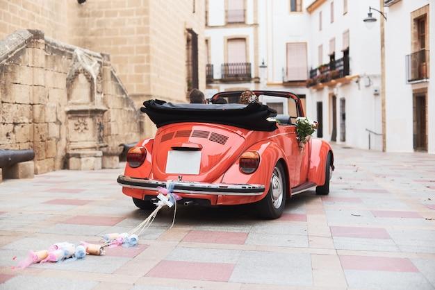 Coche rojo retro clásico de la boda y recienes casados dentro.